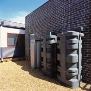 Grey rain water collection tanks behind brick building. facade, black