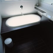 White bath with dark timber surround and flooring. bathroom, bathroom sink, floor, plumbing fixture, product design, sink, toilet, toilet seat, black, gray
