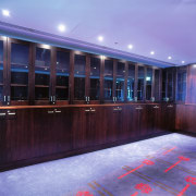 Room with dark timber cabinets along walls. - light, lighting, blue