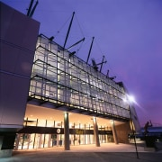 Exterior view of MCG stadium showing lighting. - architecture, building, commercial building, condominium, convention center, corporate headquarters, daylighting, evening, facade, headquarters, landmark, metropolis, metropolitan area, mixed use, night, reflection, residential area, sky, structure, tourist attraction, blue, purple