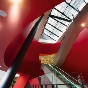 Escalator area with large red conical drum surround angle, architecture, ceiling, daylighting, design, interior design, line, red, structure, red