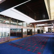 Function room with blue and red flooring, bronze-finished architecture, ceiling, interior design, leisure centre, sport venue, structure, black, blue