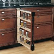 Brown wood kitchen cabinetry with pull out spice cabinetry, chest of drawers, drawer, filing cabinet, furniture, hardwood, shelf, shelving, wood stain, red