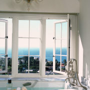 view of this bathroom featuring featuring raised bathtub ceiling, daylighting, door, estate, home, interior design, living room, structure, window, gray, white