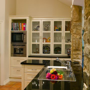 view of this french influenced kitchen featuring glass cabinetry, countertop, interior design, kitchen, room, brown, orange