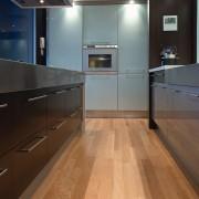 view of the kitchen featuring darkwood veneer wall, cabinetry, countertop, floor, flooring, hardwood, interior design, kitchen, laminate flooring, wood, wood flooring, gray, black