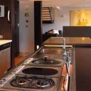 view of the kitchen featuring darkwood veneer wall, countertop, interior design, kitchen, room, black, brown