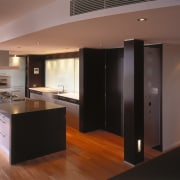 view of the kitchen featuring darkwood veneer wall, cabinetry, countertop, floor, flooring, hardwood, interior design, kitchen, real estate, room, wood flooring, black, brown
