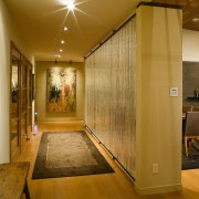 view of the hallway featuring timber flooring, rug, ceiling, floor, flooring, home, interior design, lobby, real estate, room, wall, wood, brown