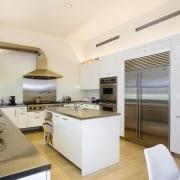 view of this kitchen featuring  travertie flooring, countertop, interior design, kitchen, real estate, white