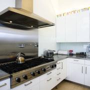 view of this kitchen featuring  travertie flooring, countertop, cuisine classique, floor, interior design, kitchen, kitchen stove, room, white