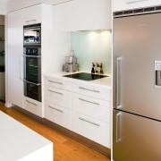 White kitchen with stainless steel refrigerator. - White countertop, home appliance, interior design, kitchen, major appliance, room, white