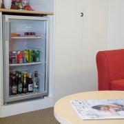 A view of a Haier mini fridge. - furniture, home appliance, product, refrigerator, shelf, shelving, gray