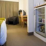 A view of a Haier mini fridge. - bedroom, floor, flooring, furniture, interior design, real estate, room, suite, brown