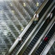 view of the builinding atrium featuring a sculptural architecture, building, daylighting, escalator, line, metal, metropolis, metropolitan area, reflection, skyscraper, steel, urban area, gray, black
