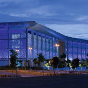 view of the exterior and glass facade of architecture, blue, building, city, commercial building, convention center, corporate headquarters, facade, headquarters, hotel, landmark, lighting, metropolis, mixed use, night, performing arts center, sky, sport venue, structure, tourist attraction, blue