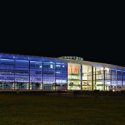view of the exterior and glass facade of architecture, building, city, convention center, corporate headquarters, facade, headquarters, night, sky, sport venue, structure, black