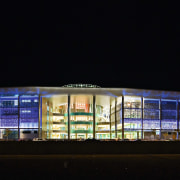 view of the exterior and glass facade of architecture, building, convention center, corporate headquarters, facade, light, lighting, night, opera, performing arts center, sport venue, stage, structure, tourist attraction, black