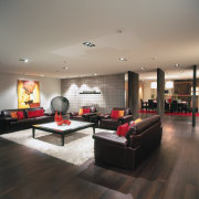 view of the lounge area featuring darked stained ceiling, floor, flooring, interior design, living room, lobby, room, table, wood flooring, gray, black