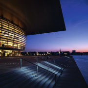 An exteior view of the building. - An architecture, atmosphere, building, city, cityscape, convention center, corporate headquarters, dawn, dusk, evening, headquarters, horizon, landmark, metropolis, metropolitan area, night, opera house, performing arts center, reflection, sky, structure, sunlight, sunset, water, blue, black