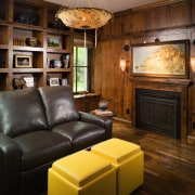 Image of lounge, featuring a fireplace, leather couches fireplace, flooring, furniture, hardwood, home, interior design, living room, room, wall, wood, wood burning stove, wood flooring, brown, black
