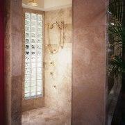 A view of the shower stall. - A bathroom, door, floor, flooring, home, interior design, plaster, plumbing fixture, room, tile, wall, window, brown