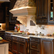 A view of a kitchen and bathroom by cabinetry, countertop, cuisine classique, interior design, kitchen, room, under cabinet lighting, brown, black