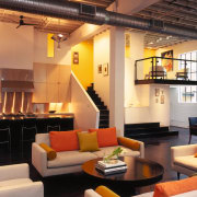 A view of the interior living area featuring ceiling, interior design, living room, loft, room, orange, black
