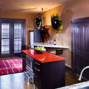 A view of this kitchen featuring black cabinetry, cabinetry, ceiling, countertop, home, interior design, kitchen, living room, room, red