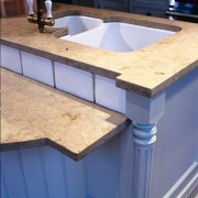 A view of this kitchen that features a countertop, material, sink, wood stain, blue, orange