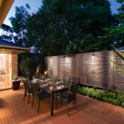 A view of this out door entertainment area backyard, courtyard, deck, estate, home, house, landscaping, lighting, outdoor structure, patio, plant, property, real estate, roof, yard, brown, black