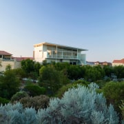Exterior view of this beach house nestled amongst architecture, city, estate, home, house, landscape, neighbourhood, plant, property, real estate, residential area, sky, suburb, tree, villa, teal