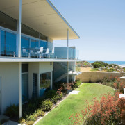 Exterior view of this beach house nestled amongst apartment, balcony, condominium, cottage, estate, home, house, property, real estate, resort, villa, teal