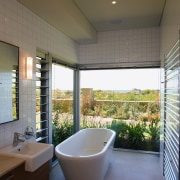 View of this bathroom featuring freestanding bathtub, floor architecture, bathroom, ceiling, daylighting, estate, home, house, interior design, real estate, room, window, gray, brown