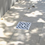 A view of some swimming pool grates. - floor, font, line, pattern, road surface, gray, white