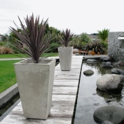 A view of some planters by Bentleigh By arecales, garden, grass, landscape, landscaping, outdoor structure, palm tree, plant, walkway, gray, white