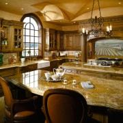A view of this elegant kitchen featuring gold cabinetry, countertop, cuisine classique, interior design, kitchen, room, brown