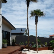 View of this outdoor enertainment area featuring landscaped agave, arecales, home, house, landscaping, outdoor structure, palm tree, plant, real estate, sky, tree, walkway, woody plant, white