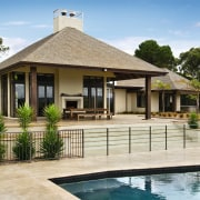 View of this outdoor pavillion that has a cottage, elevation, estate, facade, home, house, outdoor structure, property, real estate, resort, swimming pool, villa, brown, orange