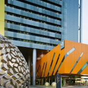 View of Brisbane square featuring bright colours, sculptured architecture, building, condominium, facade, metropolitan area, skyscraper, tower block, urban area, yellow, teal