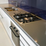 A view of this kitchen featuring the latest countertop, kitchen, kitchen stove, sink, white
