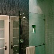 The frameless glass shower stall blends almost seamlessly bathroom, daylighting, floor, glass, plumbing fixture, public toilet, room, shower, tile, toilet, wall, green