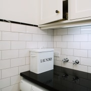 The laundry chute ends in an upper cupboard cabinetry, countertop, floor, home appliance, interior design, kitchen, kitchen stove, product design, room, tile, white