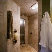 A view of this bathroom features a steam bathroom, ceiling, floor, flooring, interior design, plumbing fixture, room, tile, brown