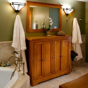 A view of this bathroom features a steam bathroom, cabinetry, chest of drawers, floor, flooring, furniture, home, interior design, room, brown