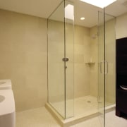 A view of this bathroom featuring glass shower bathroom, floor, glass, plumbing fixture, room, shower, orange