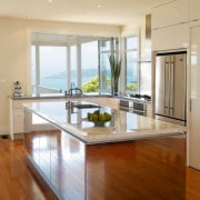 The intention was to design a kitchen that cabinetry, ceiling, countertop, floor, flooring, hardwood, interior design, kitchen, laminate flooring, living room, real estate, room, table, window, wood, wood flooring, orange, brown