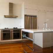 Drawers and cabinets in the island, as well architecture, cabinetry, countertop, cuisine classique, floor, flooring, hardwood, interior design, kitchen, laminate flooring, room, wood, wood flooring, brown, gray
