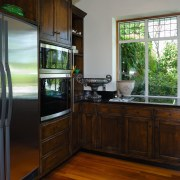 A view of this kitchen feautring solida aged countertop, home, house, kitchen, real estate, room, window, wood, black