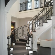 The curving staircase connects with a wide second-floor baluster, handrail, home, interior design, iron, stairs, structure, gray, black